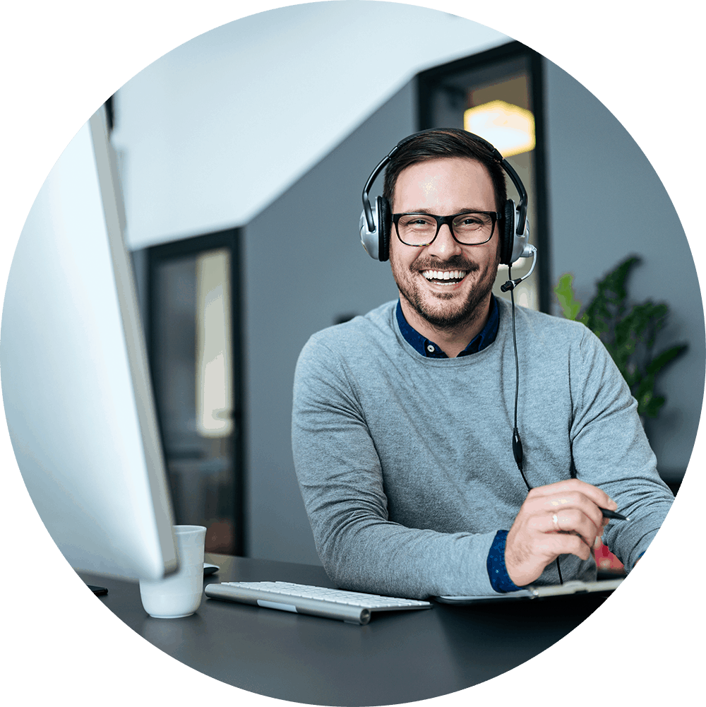 A smiling man wearing his headphones while working at his desk